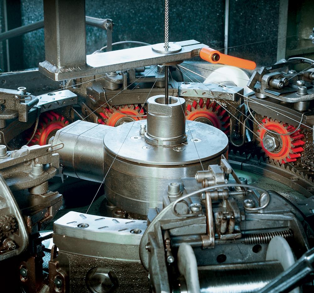 Rys. 1. Proces produkcji kabla ekranowanego: kabel przechodzi przez maszynę, która nakłada oplot na przewody kabla, a następnie wysyła go do ekstrudera, który nałoży warstwę zewnętrzną izolacji