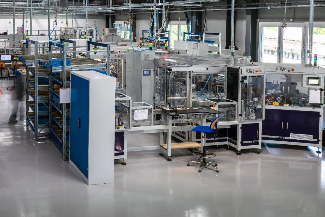 Rys. 2. Początek zautomatyzowanej linii produkcyjnej EFI-P: przekładniki Ferrantiego dostarczane są do stanowiska A, gdzie są instalowane w obudowach wyłączników i wlutowywane do elektronicznej płytki drukowanej. Przewody fazowe przechodzące przez środek przekładnika wlutowywane są do zacisków górnych oraz do miedzianych wsporników styków ruchomych